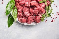 Carne cruda tajada de la carne de vaca en el cuenco blanco con las hierbas frescas en fondo de madera ligero Fotografía de archivo