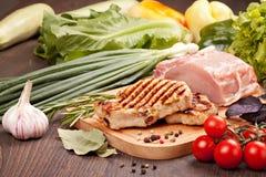 Carne cruda y asada a la parrilla con las verduras Imágenes de archivo libres de regalías