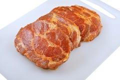 Carne, cuello del cerdo en adobo y en un boardon que taja, en un fondo blanco Fotografía de archivo