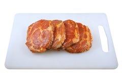 Carne, cuello del cerdo en adobo y en un boardon que taja, en un fondo blanco Foto de archivo
