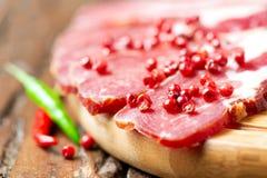 Carne curada com pimenta no fim de madeira da tabela acima imagens de stock