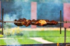 A carne da carne de porco prepara-se em um espeto no fogo na jarda no verão O fumo dá o piquancy à carne fotografia de stock