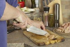 Carne da galinha dos trabalhos de casa, cortando a faixa do peito de frango, mesa de cozinha Imagem de Stock