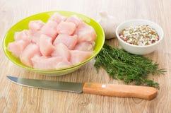 Carne da galinha na bacia, em especiarias, no alho, no aneto e na faca verdes Imagens de Stock
