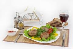 Carne da carne, rhizol redondo Costoletas redondas da carne com verdes, tomates e um vidro do vinho Café da manhã útil e saboroso imagem de stock