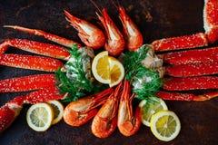 Carne de caranguejo, camarões, limão e verdes em uma tabela escura Fotografia de Stock Royalty Free