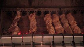 A carne de carne de porco é cozinhada em espetos no forno dentro filme