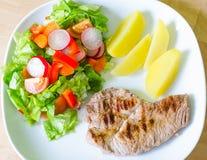 Carne de carne de porco com salada e batatas Fotografia de Stock Royalty Free
