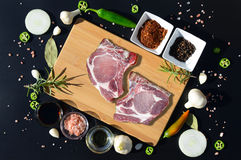 Carne de carne de porco crua em uma placa e em uma pimenta de corte Imagens de Stock