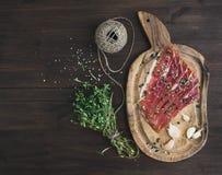 Carne de carne de porco ou prosciutto curado em uma placa rústica do woodem com garli Fotos de Stock Royalty Free