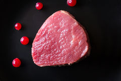 Carne de caza fresca en la placa negra y la tabla de madera Imagen de archivo libre de regalías