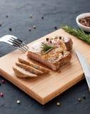 Carne de cerdo asada hecha en casa en tabla de cortar con los cubiertos, las hierbas y las especias Foto de archivo