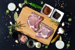 Carne de cerdo cruda en una tabla de cortar y una pimienta Imagenes de archivo