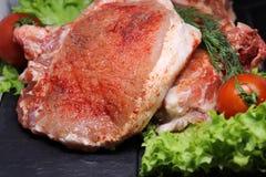 Carne de cerdo cruda, hermosa y fresca en el hueso asperjado con paprika y pimienta imágenes de archivo libres de regalías