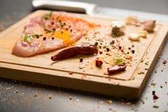 Carne de cerdo fresca cruda a bordo con los condimentos en fondo oscuro Imagenes de archivo