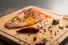 Carne de cerdo fresca cruda a bordo con los condimentos en fondo oscuro Imagen de archivo