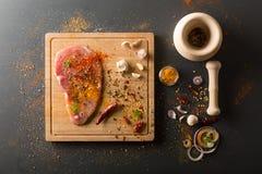Carne de cerdo fresca cruda a bordo con los condimentos en fondo oscuro Fotografía de archivo