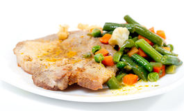 Carne de cerdo frita con las verduras en la placa blanca. Fotos de archivo