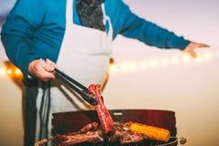 Carne de cocinar mayor en la barbacoa - cocinero que asa a la parrilla la carne y que sirve las salchichas en la cena en tejado - fotos de archivo