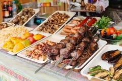 carne de la carne asada en los pinchos en el fuego abierto Kebab asado a la parrilla en el pincho del metal Comida de la calle foto de archivo libre de regalías