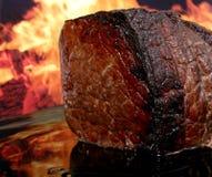 Carne de la carne asada del inglés por el fuego con las llamas Fotografía de archivo libre de regalías