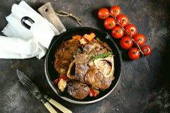 Carne de Ossobuko com cebolas, cenouras, aipo, vinho branco e tomilho Foto de Stock
