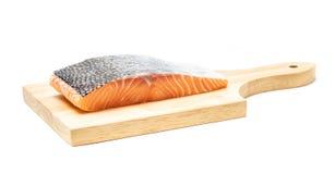 Carne de pescados de color salmón en la tabla de cortar de madera imagen de archivo libre de regalías