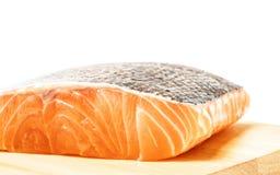 Carne de pescados de color salmón en la tabla de cortar de madera fotos de archivo