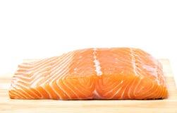 Carne de pescados de color salmón en la tabla de cortar de madera imagenes de archivo