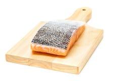 Carne de pescados de color salmón en la tabla de cortar de madera foto de archivo
