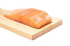 Carne de pescados de color salmón en la tabla de cortar de madera fotografía de archivo libre de regalías