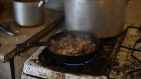 A carne de carne de porco é fritada em uma frigideira em um fogão de gás velho, fim filme