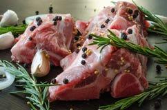 Carne de carne de porco com pimenta preta na parte superior e nos alecrins com alho Fotografia de Stock Royalty Free