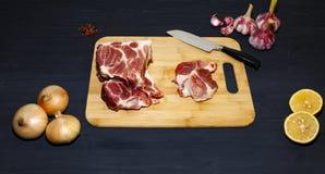 Carne de carne de porco crua em uma superf?cie de madeira preta e em ingredientes para cozinhar Fundo do alimento com espa?o da c fotografia de stock