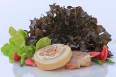 Carne de porco crua na placa e nos vegetais de corte Fotografia de Stock Royalty Free