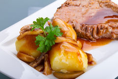Carne de porco de assado com molho e batatas Fotografia de Stock Royalty Free