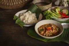 A carne de porco do estilo e o tomate do norte tailandeses Chili Relish, ONG do prik do nam na bacia branca na tabela de madeira  foto de stock royalty free