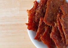 Carne de porco espasmódica em uma bacia branca em uma tabela Fotos de Stock