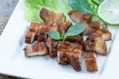 Carne de porco friável com alho e pimenta na placa branca Fotografia de Stock
