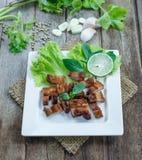 Carne de porco friável com alho e pimenta na placa branca Imagem de Stock