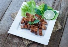Carne de porco friável com alho e pimenta na placa branca Imagem de Stock Royalty Free