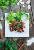Carne de porco friável com alho e pimenta na placa branca Fotos de Stock Royalty Free