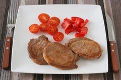 Carne de porco fritada com tomate Fotografia de Stock