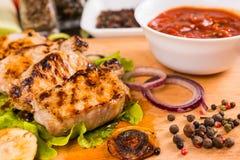 Carne de porco grelhada com a bacia de salsa e de vegetais Foto de Stock
