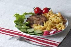 Carne de carne de porco na grade com batatas e os legumes frescos fritados Fotografia de Stock Royalty Free