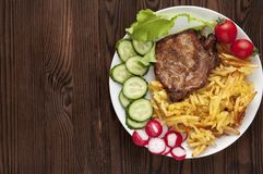 Carne de carne de porco na grade com batatas e os legumes frescos fritados em uma placa branca Fotos de Stock