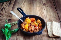 Carne de porco Roasted com pimenta doce, tomates e manjericão na madeira Foto de Stock Royalty Free