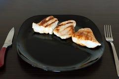 Carne de Turquía hecha en parrilla Cuchillo y bifurcación de la placa negra travieso Foto de archivo