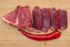 Carne de vaca cortada cruda fresca de la carne en una tabla de cortar de madera Fotografía de archivo libre de regalías