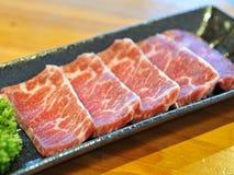 Carne de vaca cortada cruda fresca en el disco negro fotos de archivo